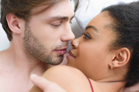 Photo pour Portrait de tendres multiethnique jeune couple amoureux au lit ensemble matin - image libre de droit