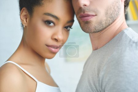 partial view of multiethnic couple in love at home