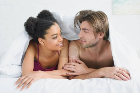 portrait of smiling multiethnic young couple in love lying under blanket together in bed in morning