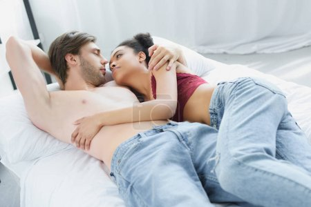 multiethnic young couple in love looking at each other while lying in bed together in morning