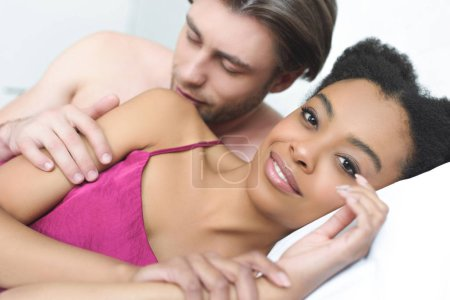 portrait of multiethnic young couple in love lying in bed together in morning