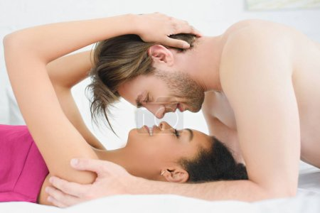 side view of young interracial couple lying in bed in morning at home