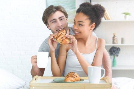 Photo pour Portrait de couple jeune multiraciale, prenant son petit déjeuner au lit dans la matinée à la maison - image libre de droit