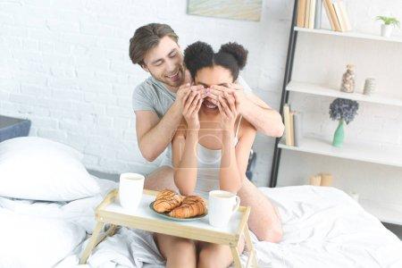 Foto de Pareja joven multirracial desayunando en la cama en la mañana en casa - Imagen libre de derechos