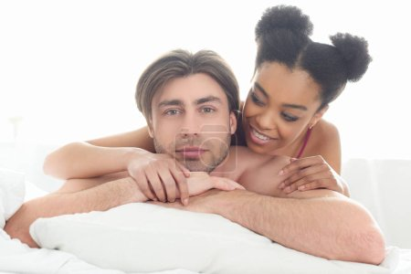 portrait of young interracial couple resting in bed together in morning at home