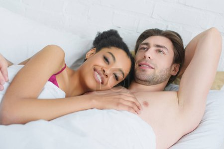portrait of young smiling interracial couple lying in bed in morning at home