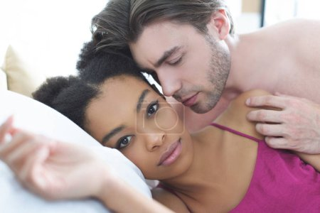 portrait of tender multiethnic young couple in love in bed at home