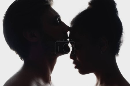 side view of silhouettes of interracial couple in love