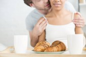 selective focus of breakfast on wooden tray and multiethnic couple at home