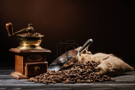 coffee grinder with beans and scoop on rustic wooden table