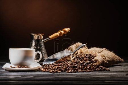 coffee cup with scoop and cezve on heap of coffee beans and on rustic wooden table