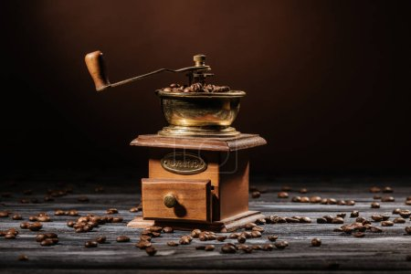 vintage coffee grinder on rustic wooden table spilled with coffee beans