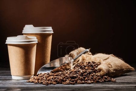 close-up shot of paper cups with scoop and heap of coffee beans on rustic wooden table
