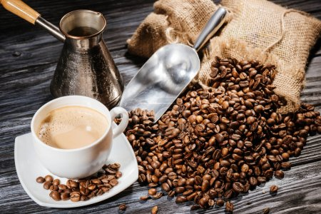 high angle view of coffee cup with scoop and cezve on heap of coffee beans and on rustic wooden table