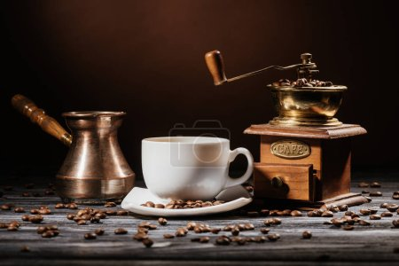 close-up shot of cup with cezve and coffee grinder on rustic wooden table