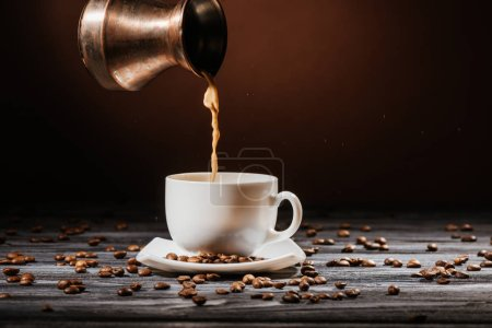 Photo for Close-up shot of coffee pouring from cezve into cup on rustic wooden table - Royalty Free Image