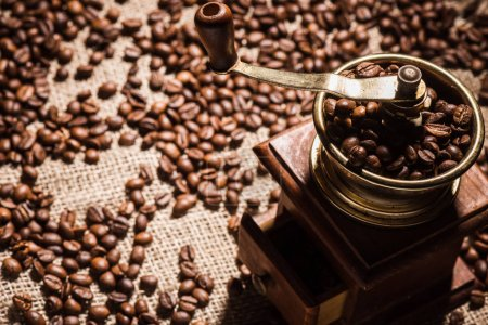 close-up shot of coffee grinder on sackcloth spilled with coffee beans