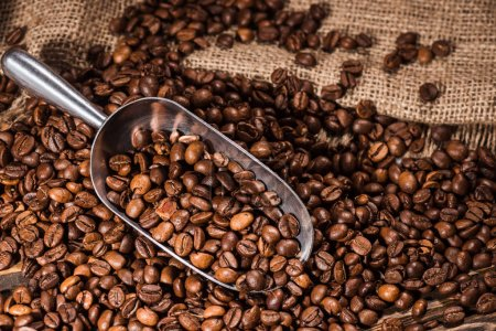 close-up shot of scoop and roasted coffee beans spilled on sackcloth
