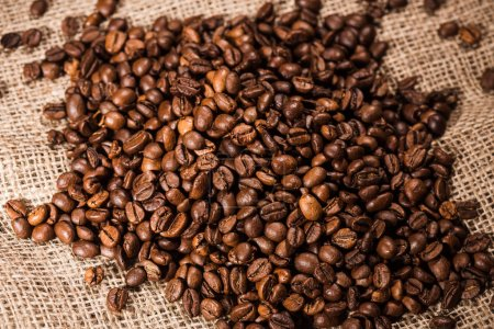 close-up shot of heap of roasted coffee beans on sackcloth