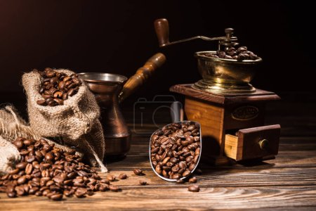 Photo for Metal scoop, vintage cezve and coffee grinder on rustic wooden table spilled with roasted beans - Royalty Free Image