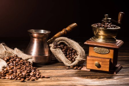 vintage cezve and coffee grinder on rustic wooden table spilled with roasted beans