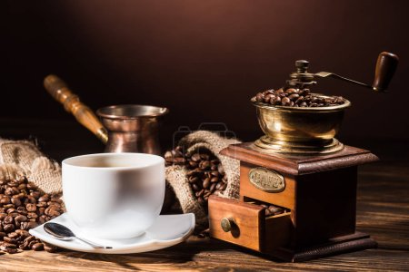 coffee cup with vintage cezve and coffee grinder on rustic wooden table