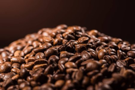 close-up shot of heap of roasted coffee beans on dark brown background