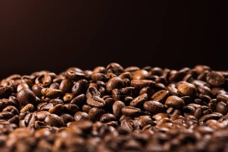 close-up shot of heap of roasted coffee beans isolated on black