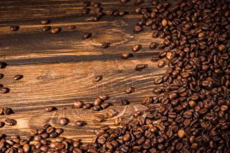 top view of roasted coffee beans spilled on rustic wooden table