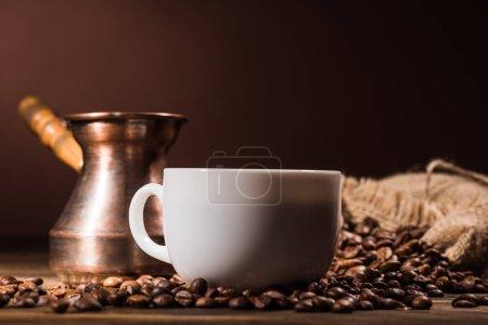 Photo pour Gros plan de la tasse de café avec les grains torréfiés et cezve vintage - image libre de droit