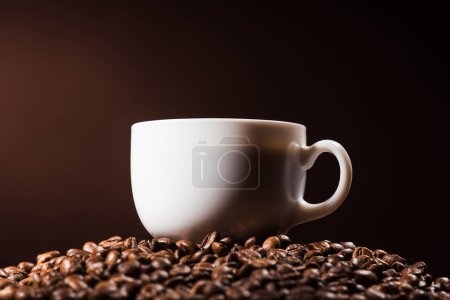 close-up shot of cup standing on heap of coffee beans on dark brown background