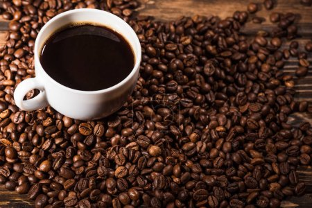 high angle view of cup with coffee beans on rustic wooden table