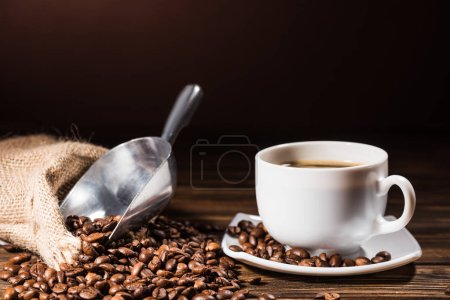 close-up shot heap of coffee beans cup and metal scoop on rustic wooden table