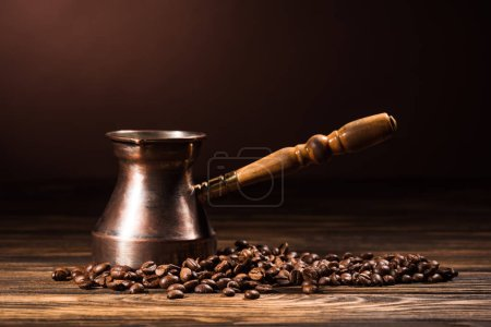 close-up shot of cezve with coffee beans on rustic wooden table