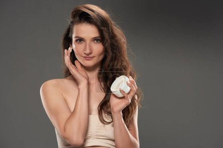 beautiful brunette woman applying moisturizing cream on face, isolated on grey