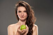 beautiful brunette girl with fresh green apple, isolated on grey