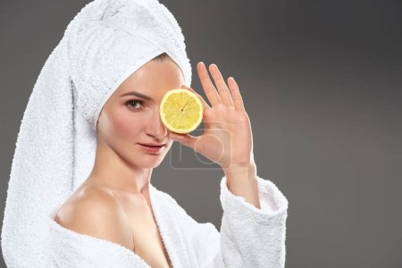 pretty girl with citrus slice in white bathrobe and towel, isolated on grey