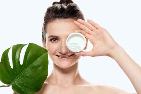 beautiful woman with face cream in plastic container and monstera leaf, isolated on white