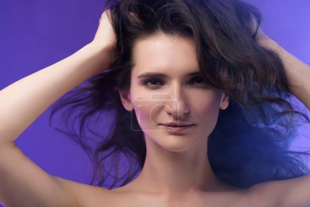 portrait of young beautiful brunette woman on purple