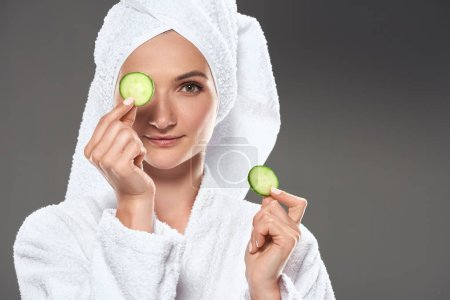 attractive girl with cucumber slices in white bathrobe and towel, isolated on grey