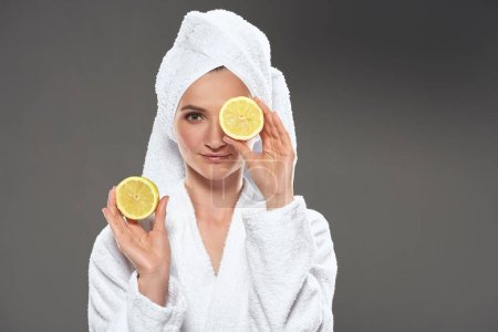 elegant girl with lemon slices in white bathrobe and towel, isolated on grey