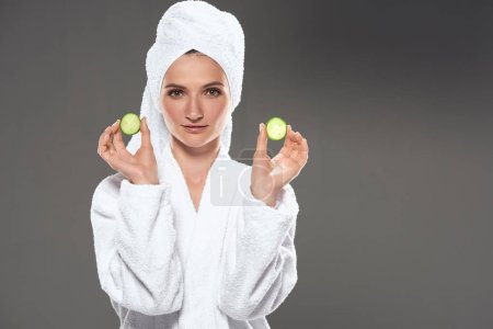 beautiful girl with cucumber slices in white bathrobe and towel, isolated on grey