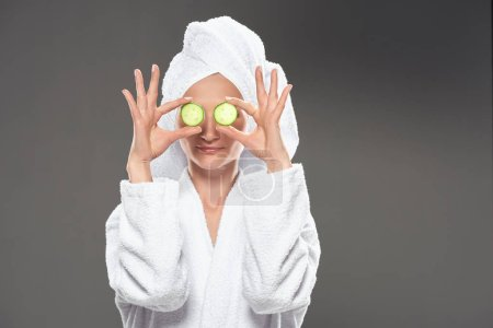 girl with cucumber slices in white bathrobe and towel on head, isolated on grey