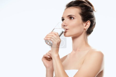 Photo for Attractive girl in towel drinking water from glass, isolated on white - Royalty Free Image