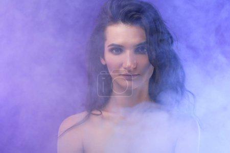 portrait of nude elegant girl in smoke on purple