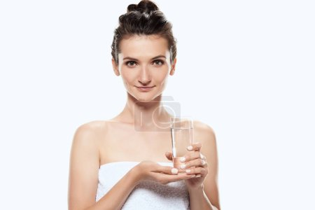 beautiful girl in towel holding glass of water, isolated on white