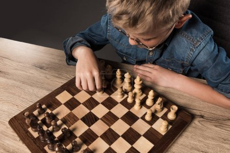 elevated view of little boy in eyeglasses playing chess at table