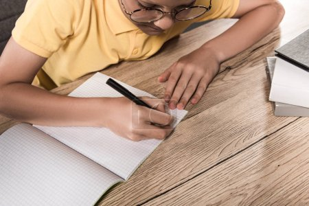 partial view of schoolboy in eyeglasses writing in empty textbook at table with stack of books