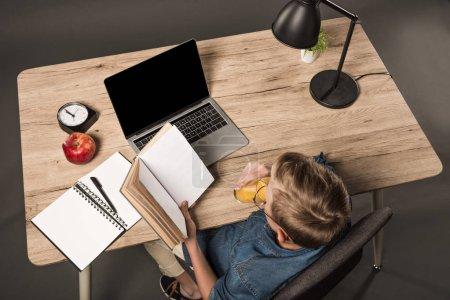 Photo pour Vue aérienne du livre de lecture de l'écolier et du jus de boisson à table avec ordinateur portable, manuel, lampe, plante, horloge et pomme - image libre de droit
