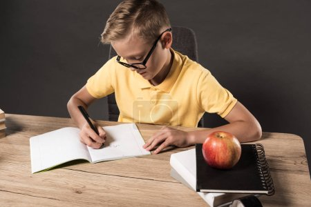 focused school boy in eyeglasses doing homework at table with books, textbooks and apple on grey background